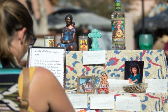 Lallania Tomlinson, of Las Cruces, looks at the Dia de los Muerto altars for Lydia Schodorf-Vandiver during the festivities on the Mesilla Plaza on Sunday, Nov. 4, 2018.