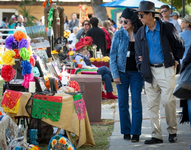 Carlos Simental and his wife Linda, of El Paso, look at the Dia de los Muertos altars on Sunday, Nov. 4, 2018, during the festivities on the Mesilla Plaza.