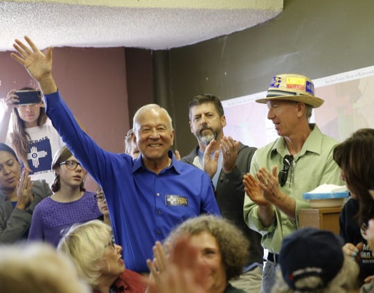 New Mexico Supreme Court judicial candidate Michael Vigil waves to supporters Sunday during a campaign stop at the Democratic Party headquarters in Farmington.