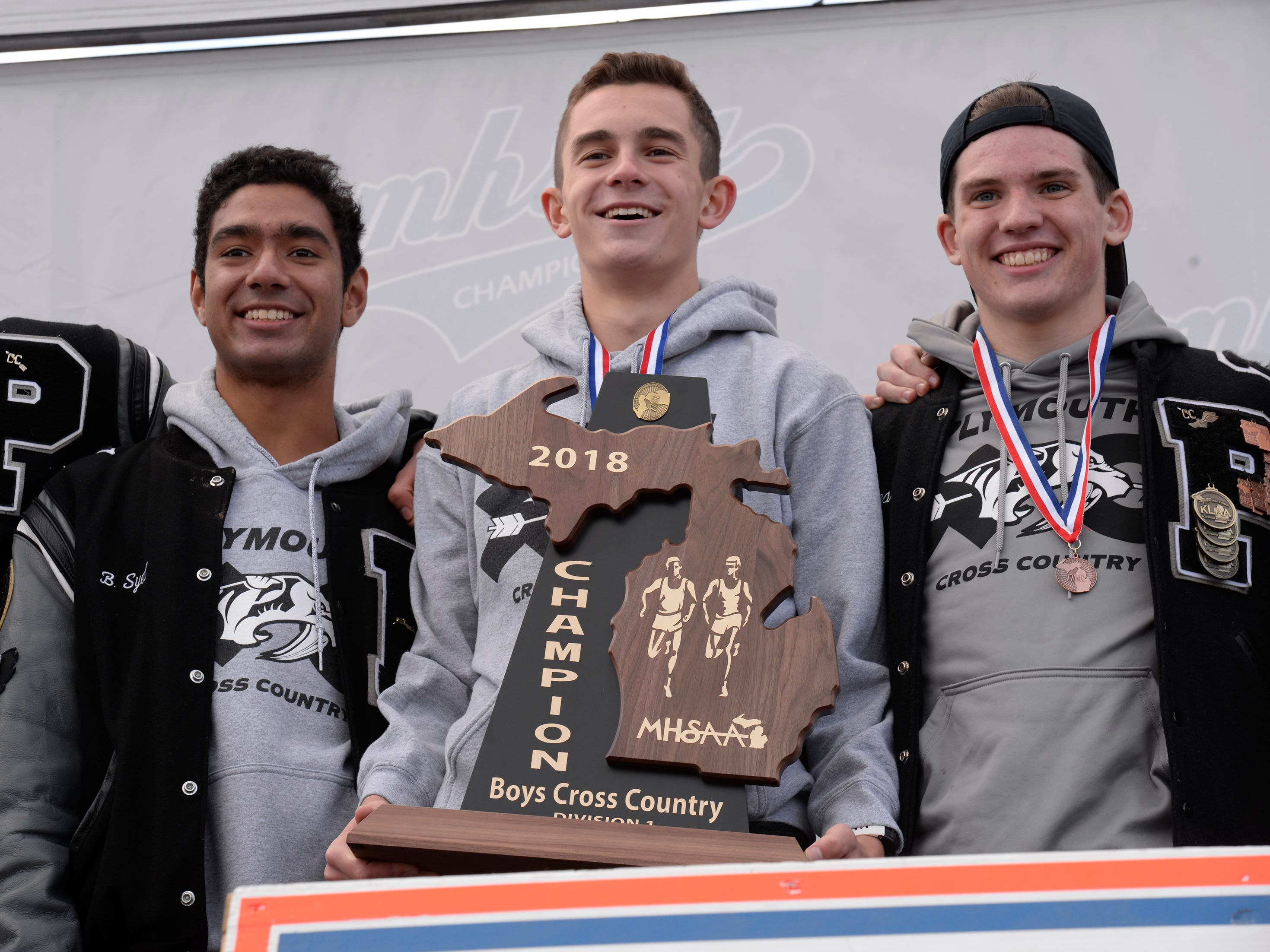 Plymouth runners Bassil Syed (left), Carter Solomon and Patrick Byrnes with Division 1 cross country team trophy.