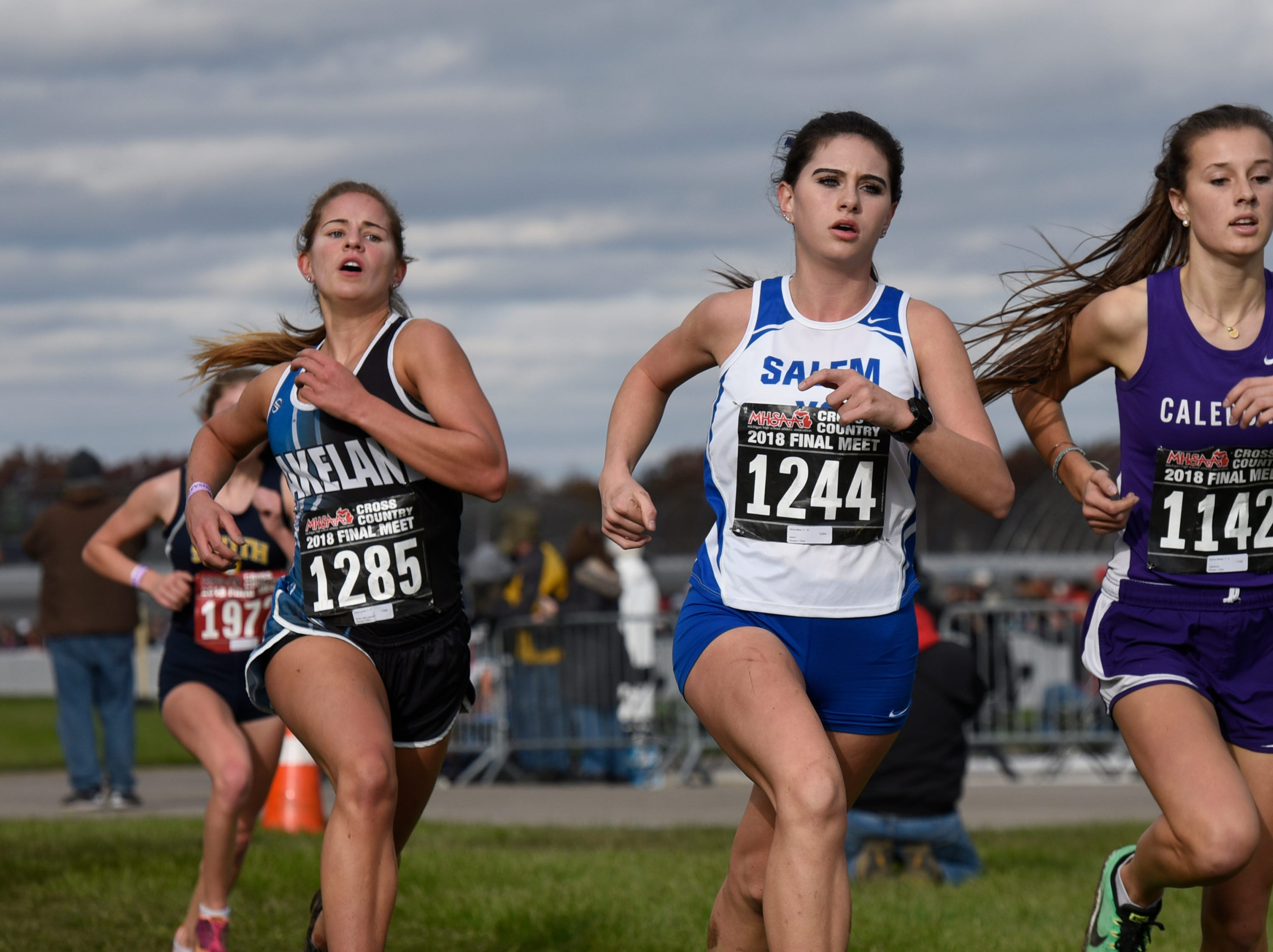 Salem's Olivia Millen (1244) and Lakeland's Rylee Lukes (1285) during the Division 1 2018 cross country finals at Michigan International Speedway.
