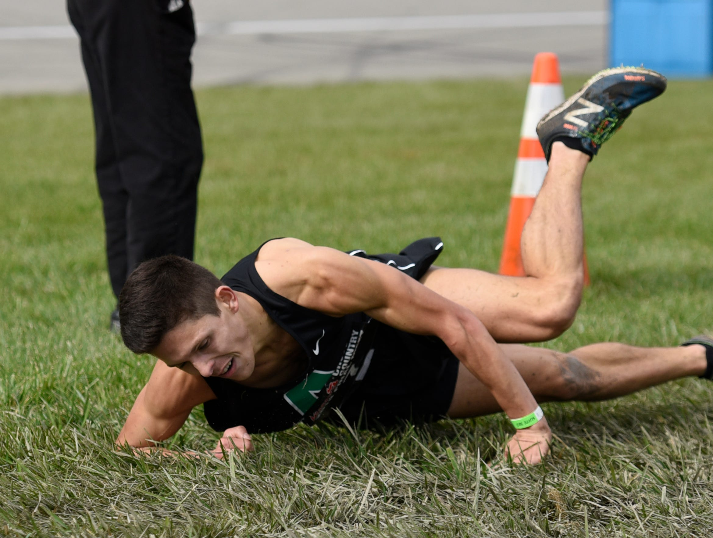 Alpena's Josh Smith takes a tumble in the soggy grass near the finish line of the Division 1 2018 cross country finals at Michigan International Speedway.