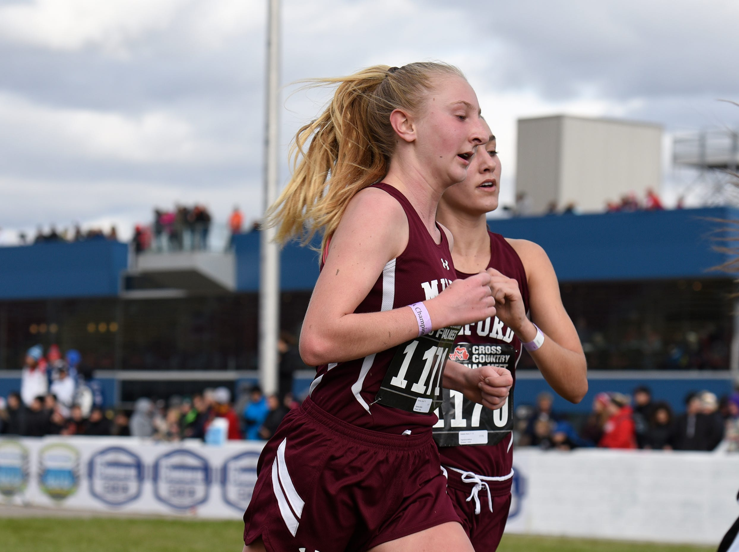 Milford's Sydney Chura (1171) and Victoria Heiligenthal during the Division 1 2018 cross country finals at Michigan International Speedway.