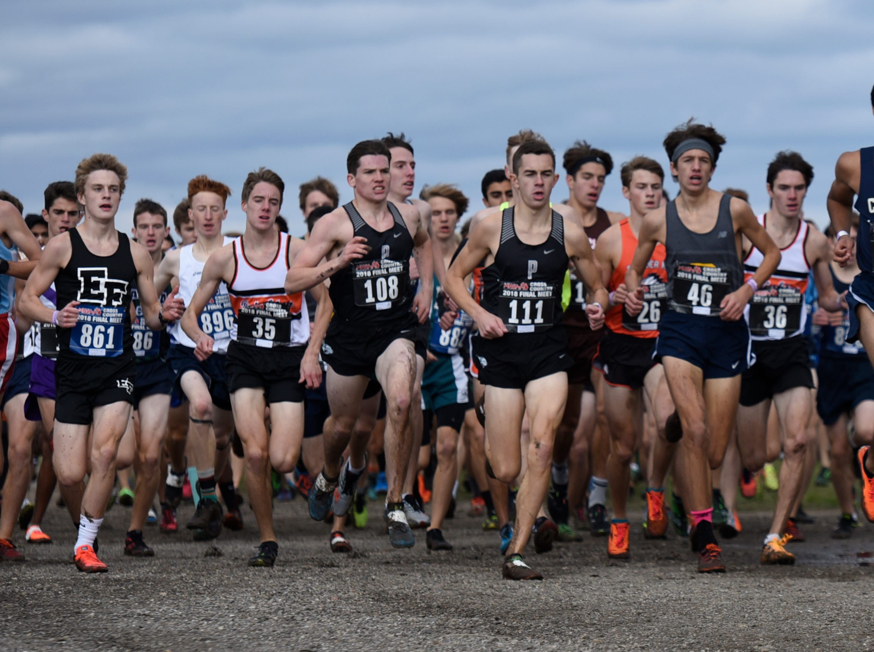 Plymouth's Patrick Barnes (108) and Carter Solomon (111) at front of the pack early in the Division 1 2018 cross country finals at Michigan International Speedway.