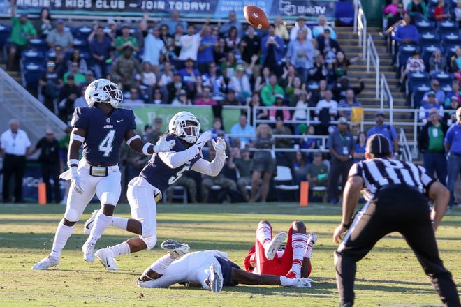 UWF's Marvin Conley (5) keeps his eye on the loose ball and makes an interception after teammate Alden McClellon, left on the ground, hit Valdosta State wide receiver Travon Roberts, right on the ground, in the Argos' last home game of the regular season on Saturday, November 3, 2018, at Blue Wahoos Stadium.