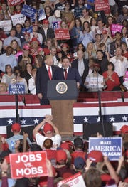 President Donald Trump looks on as Ron DeSantis, the Republican candidate for governor, speaks Saturday, Nov. 3, 2018, at a rally at the ST Engineering hangar at the Pensacola International Airport.