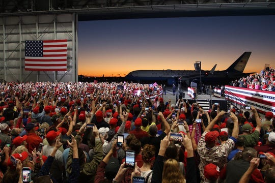 Thousands of supporters hold up their cellphones for a photo of Air Force One landing Saturday, Nov. 3, 2018, ahead of President Donald Trump's rally at the ST Engineering hangar at the Pensacola International Airport.