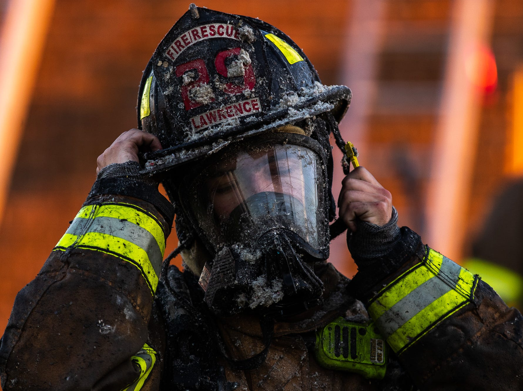 A firefighter is covered in ash as he removes his gear at the scene of a second-alarm heavily engulfed house fire with entrapment on the 800 block of Two Taverns Road, Saturday, Nov. 3, 2018, in Mount Pleasant Township. Firefighters rescued a young child from the second floor of the house while facing heavy wind-driven fire, said United Hook and Ladder Chief Steve Rabine.