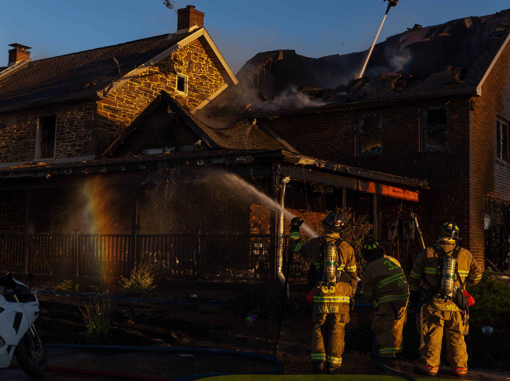 A rainbow forms as firefighters hose down the scene of a second-alarm heavily engulfed house fire with entrapment on the 800 block of Two Taverns Road, Saturday, Nov. 3, 2018, in Mount Pleasant Township. Firefighters rescued a young child from the second floor of the house while facing heavy wind-driven fire, said United Hook and Ladder Chief Steve Rabine.