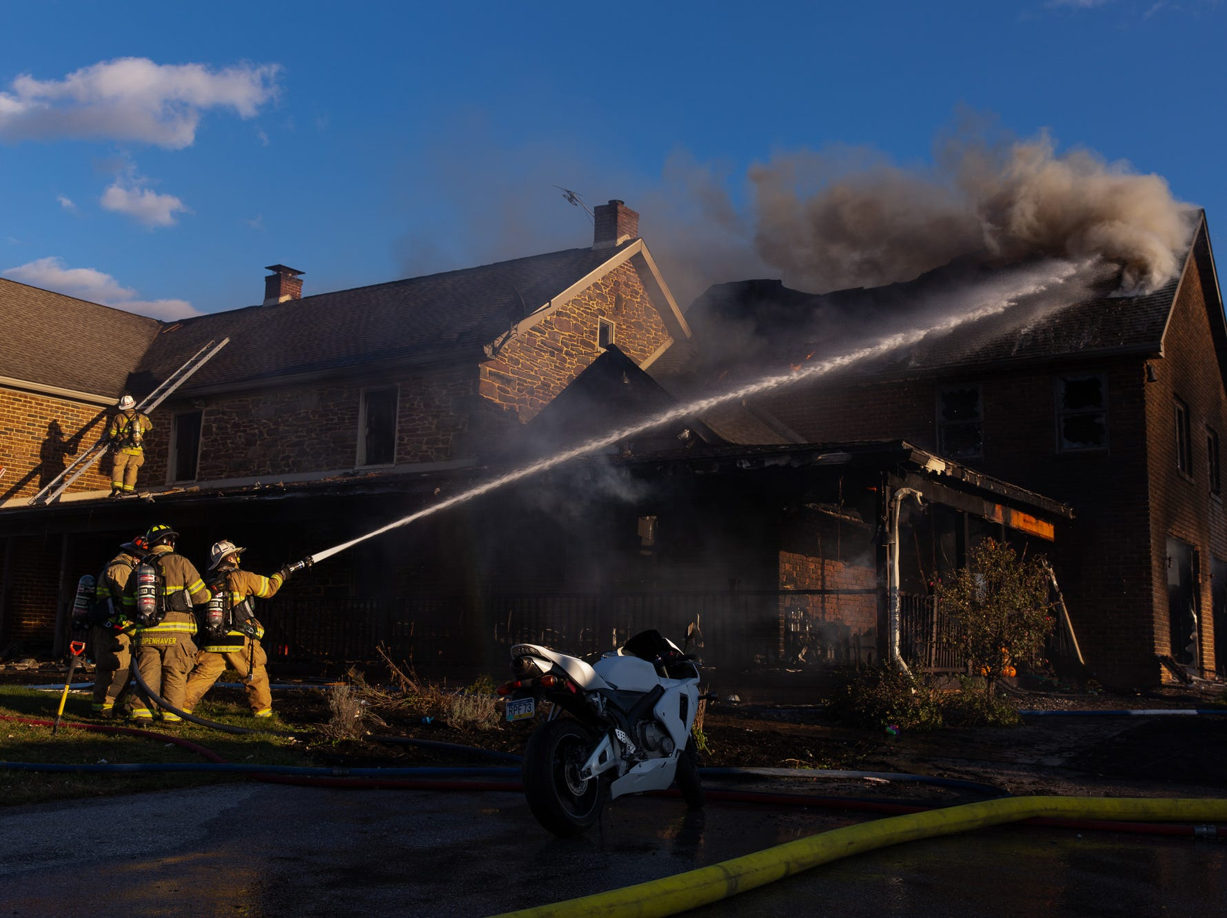Firefighters work at the scene of a second-alarm heavily engulfed house fire with entrapment on the 800 block of Two Taverns Road, Saturday, Nov. 3, 2018, in Mount Pleasant Township. Firefighters rescued a young child from the second floor of the house while facing heavy wind-driven fire, said United Hook and Ladder Chief Steve Rabine.