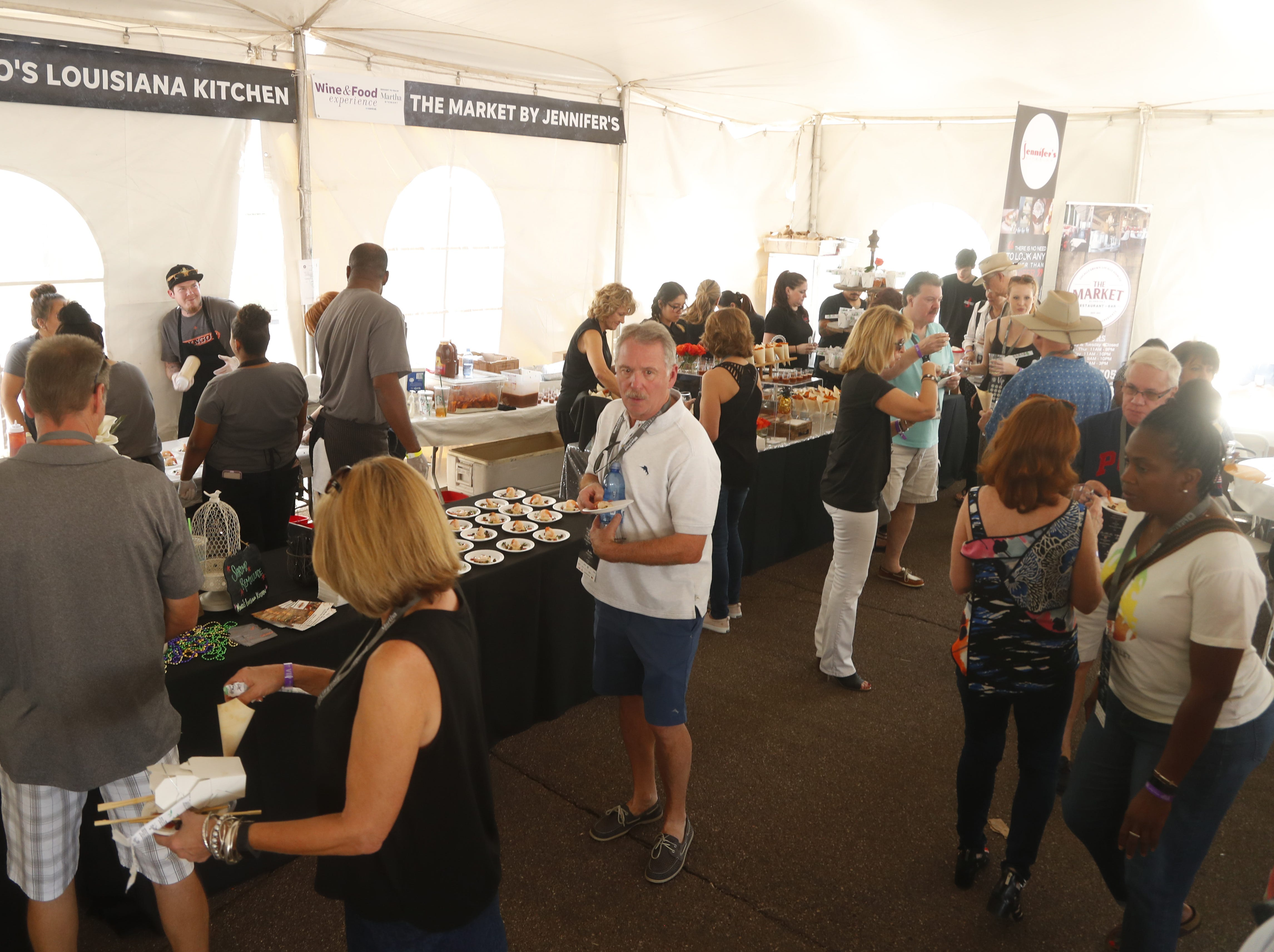 People mingle in the shade of the tent near the samples of food during the azcentral Wine & Food Experience at WestWorld of Scottsdale, Ariz. on Saturday, Nov. 3, 2018.