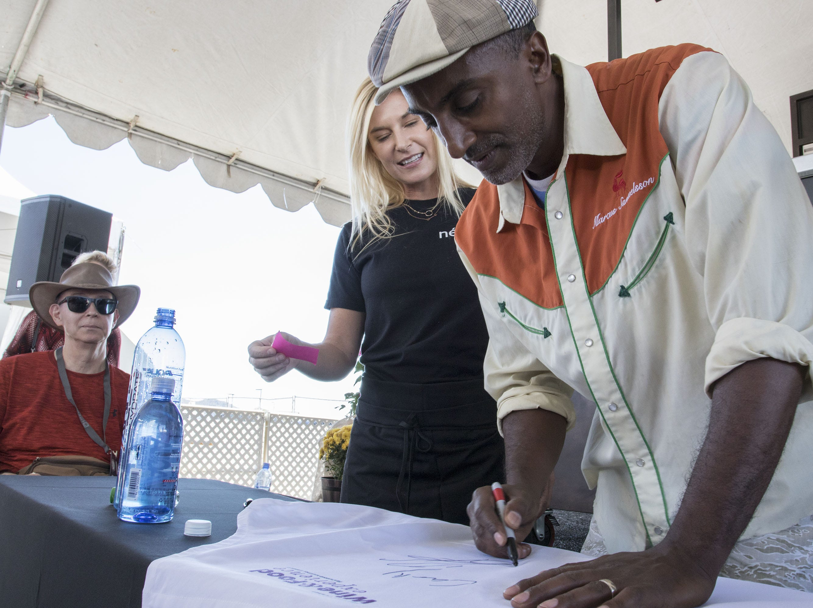 Chef Marcus Samuelsson signs an apron for a guest during the azcentral Wine & Food Experience at WestWorld of Scottsdale, Saturday, Nov. 3, 2018.