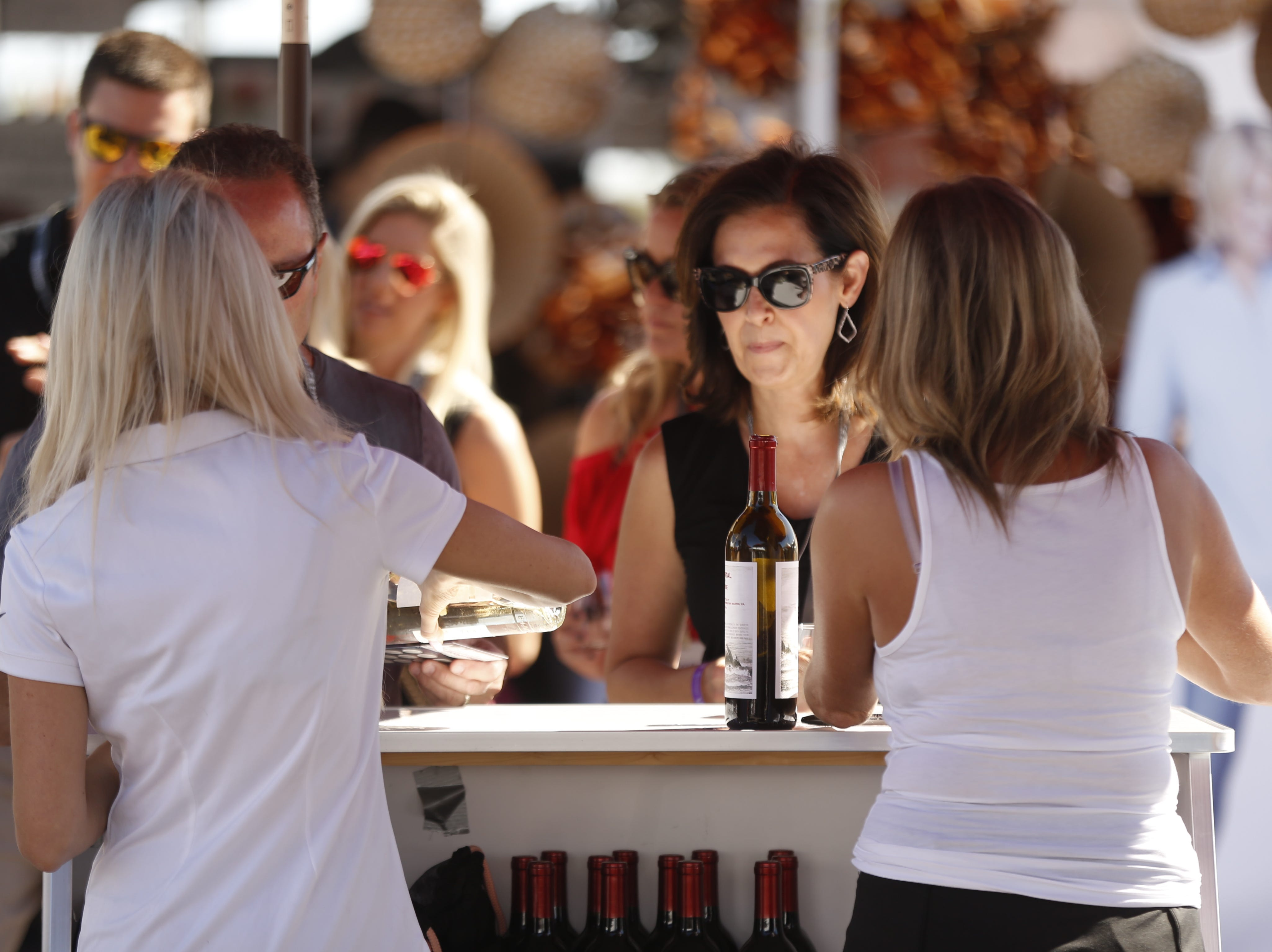 Guests get their first wine pour near the entrance during the azcentral Wine & Food Experience at WestWorld of Scottsdale, Ariz. on Saturday, Nov. 3, 2018.
