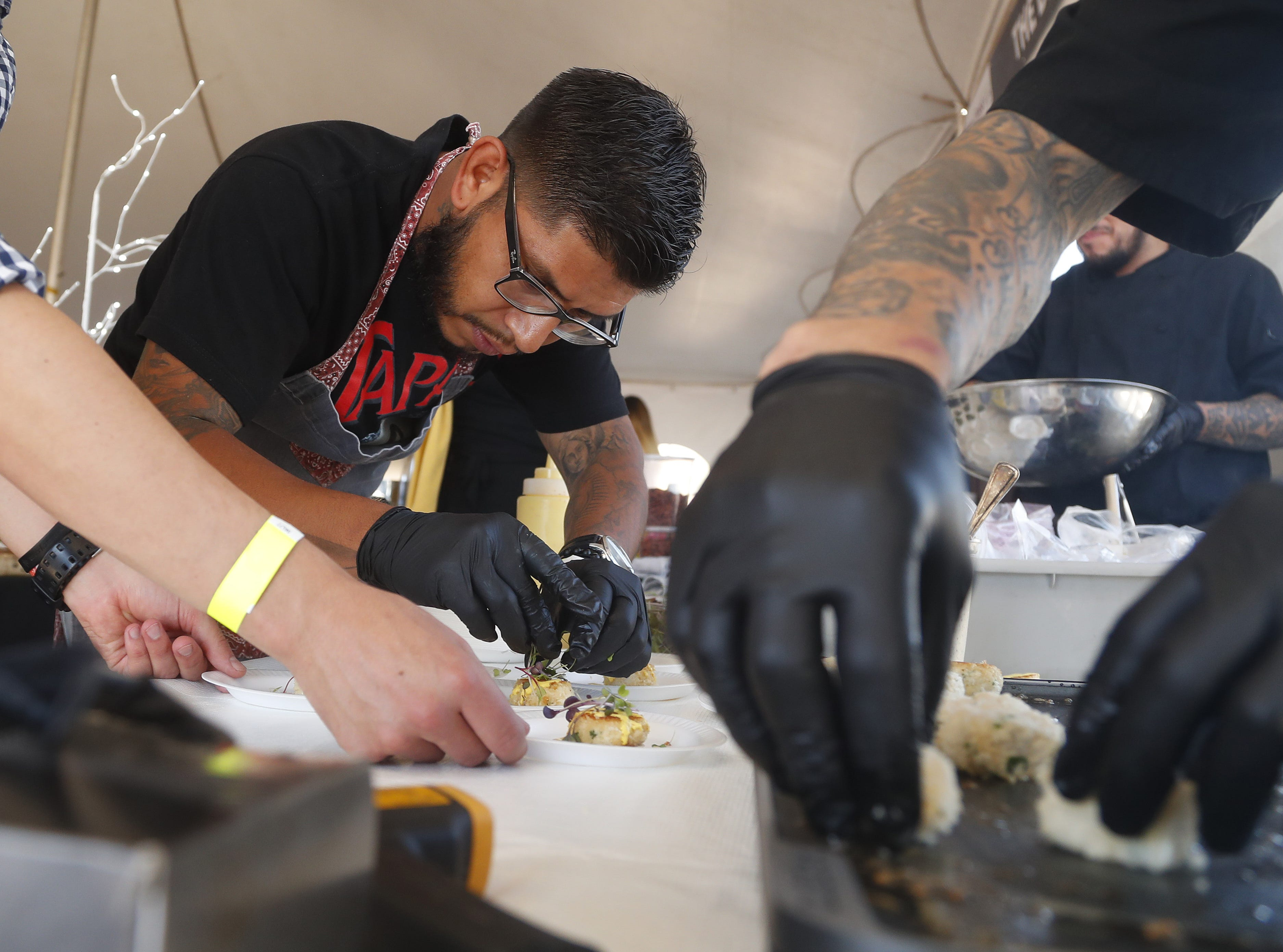 Timo Wine Bar's chef Tony Gordillo (center) preps a plate of jumbo lump crab during the azcentral Wine & Food Experience at WestWorld of Scottsdale, Ariz. on Saturday, Nov. 3, 2018.