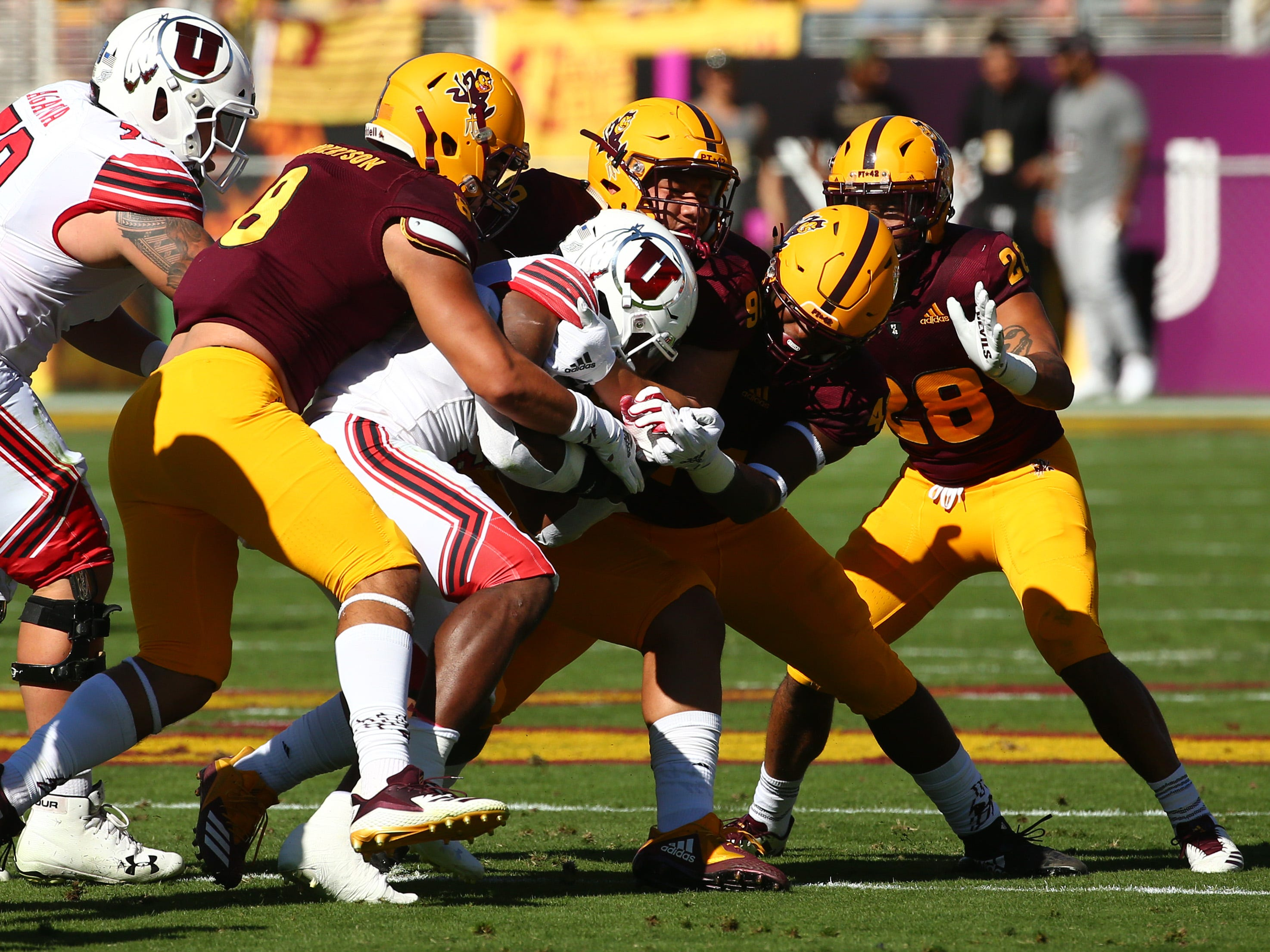 Arizona State defense tackles Utah's Zack Moss in the first half on Nov. 3 at Sun Devil Stadium.