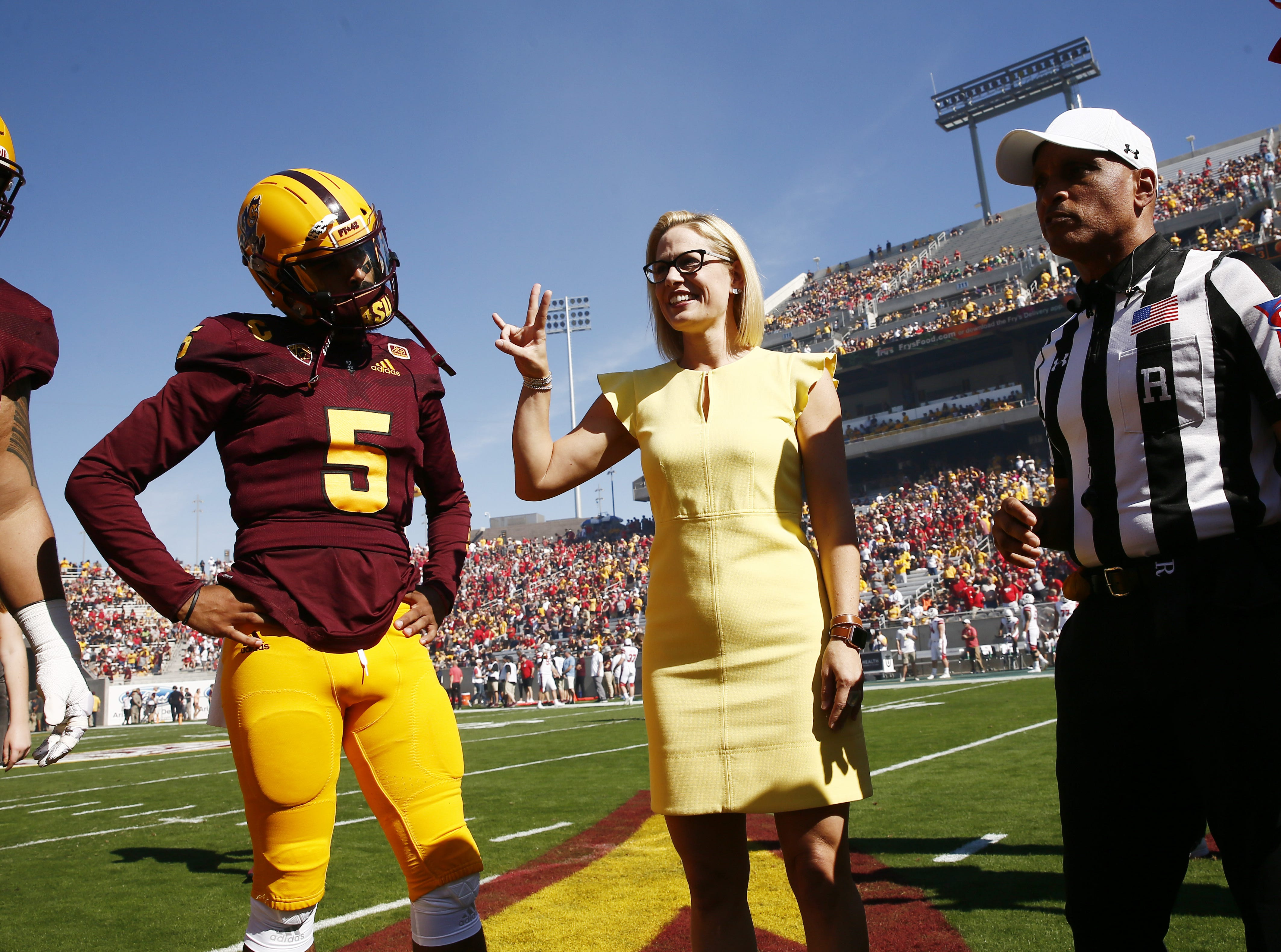 Rep. Kyrsten Sinema, D-Ariz., the Democratic candidate for the U.S. Senate in the huddle for the coin toss as Utah plays Arizona State. Sinema is running against Republication Martha McSally for the U.S. Senate.