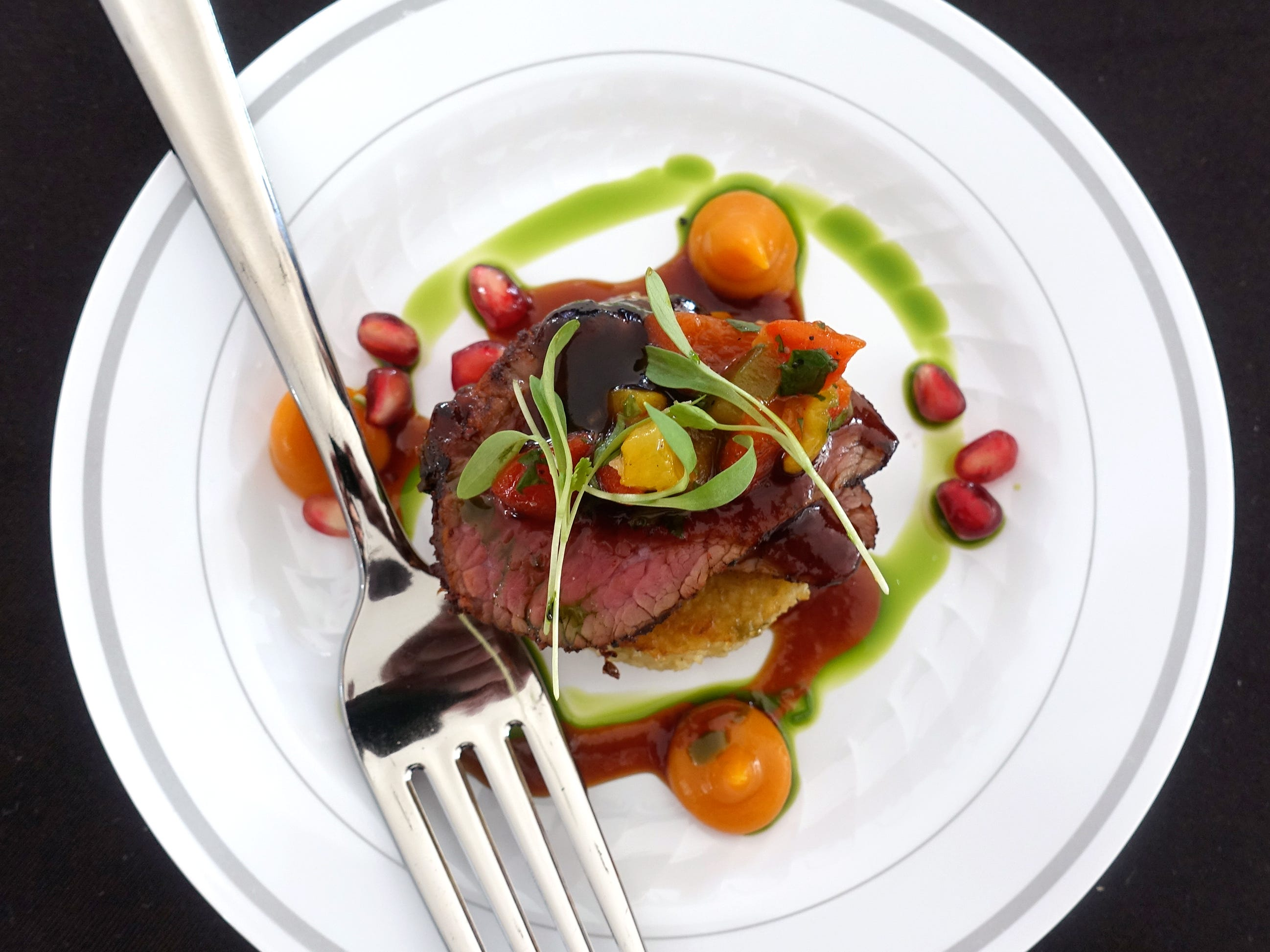 Aleppo grilled bison steak with green chile and cheddar polenta cake, smoked maple sweet potato puree and pomegranate port reduction from Different Pointe of View at azcentral Wine & Food Experience 2018 at WestWorld of Scottsdale, Sunday, Nov. 4, 2018.