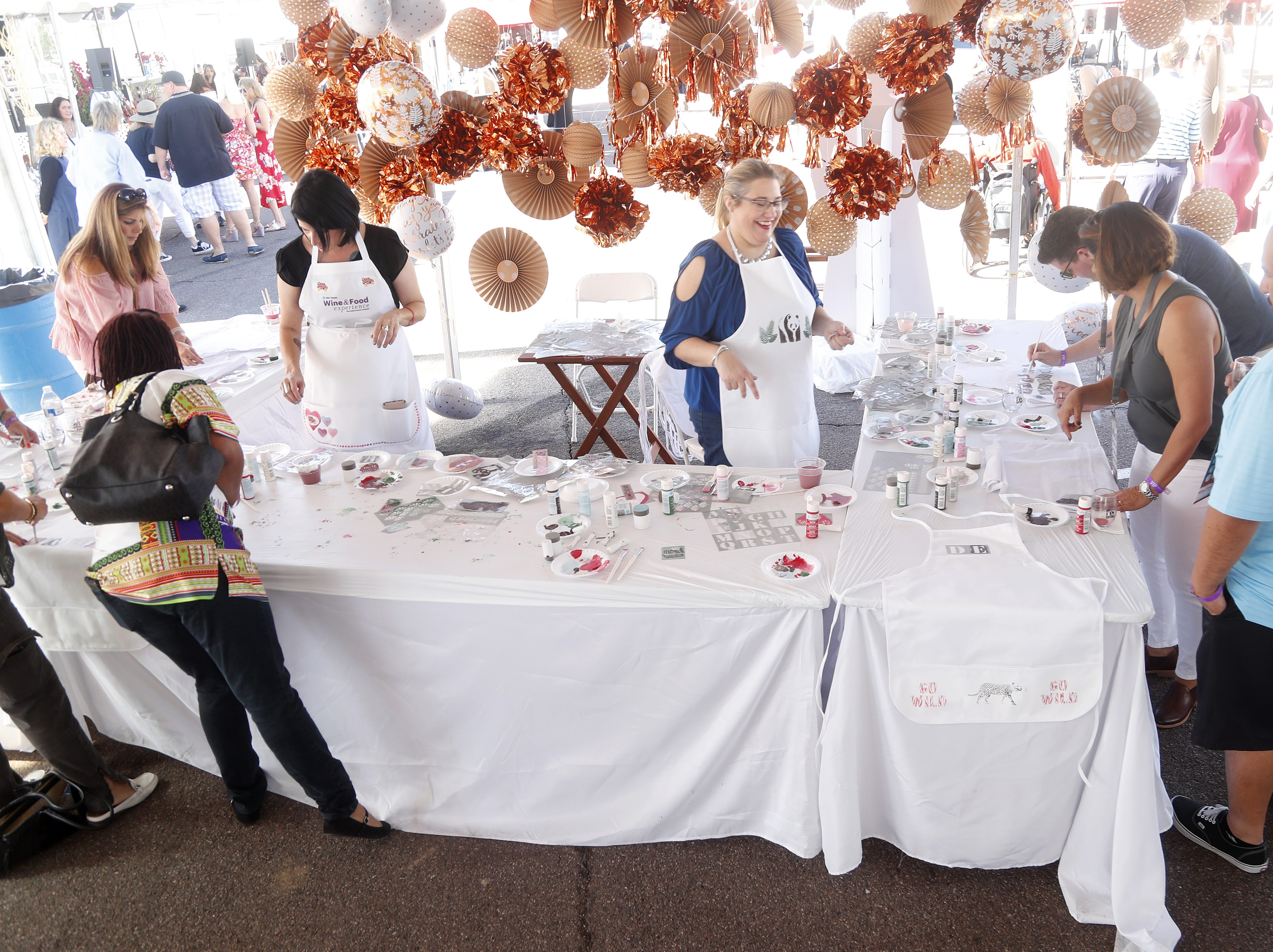 People paint their own aprons inside the Martha Stewart Living tent during the azcentral Wine & Food Experience at WestWorld of Scottsdale, Ariz. on November 3, 2018.