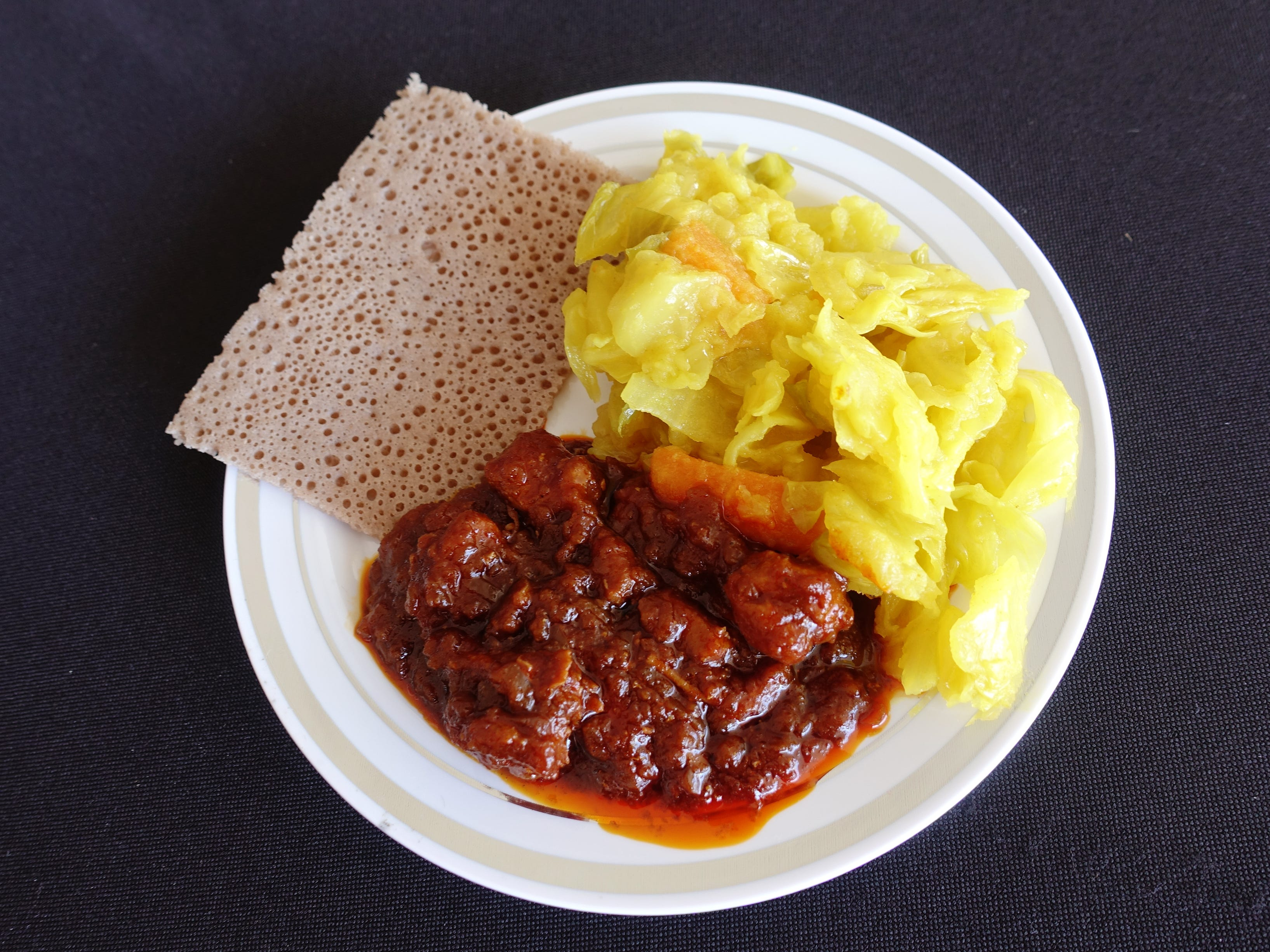 Doro wat (spicy chicken stew, bottom) and tikil gomen (cabbage with carrots and potatoes, right) with injera (Ethiopian bread, left) from Cafe Lalibela at azcentral Wine & Food Experience 2018 at WestWorld of Scottsdale, Saturday, Nov. 3, 2018.