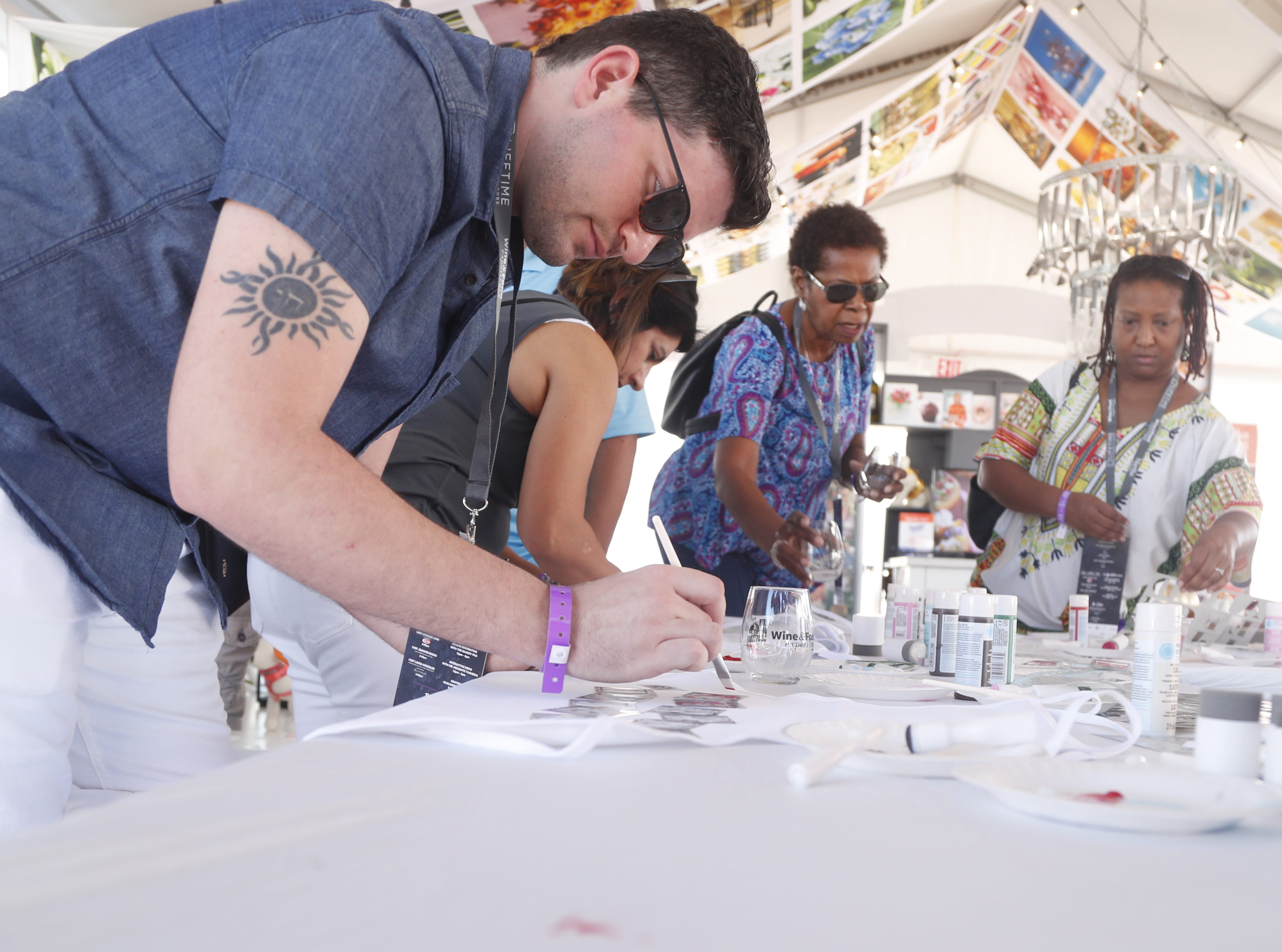 "Jared Deluca paints an apron with ""cucina deluca"" inside the Martha Stewart Living tent during the azcentral Wine & Food Experience at WestWorld of Scottsdale, Ariz. on Saturday, Nov. 3, 2018."