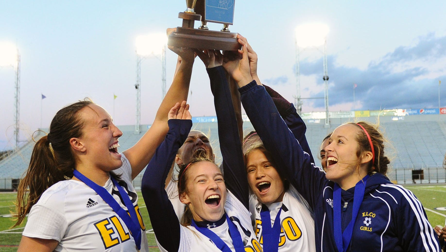 Elco players raise the District 3 2A championship trophy after Saturday's 1-0 title game win over Boiling Springs.