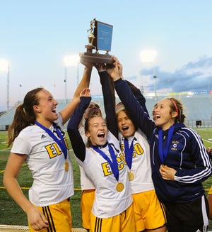 Elco players raise the District 3 2A championship trophy after their 1-0 title game win over Boiling Springs.