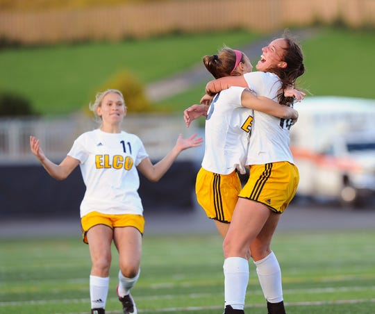 Elco's Jordan Rosengrant (23) hugs Ryelle Shuey (10) as Julia Nelson (11) rushes in to join the celebration after Shuey scores the only goal of the game on a free kick during the first half of play.