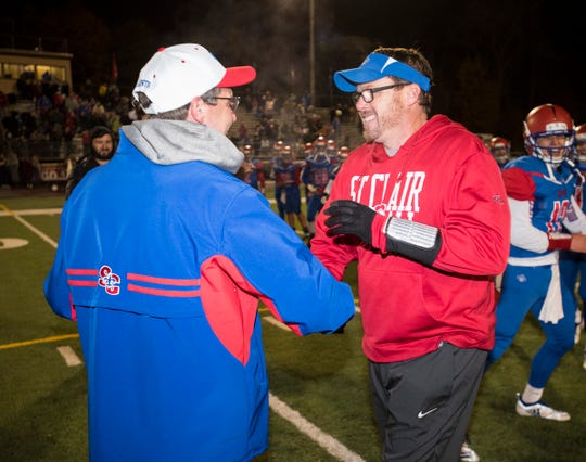 St. Clair High School athletic director Sandy Rutledge, left, shakes hands with head football coach James Bishop before handing him the MHSAA Division 4 championship trophy Saturday, Nov. 3, 2018 at East China Stadium. The Saints defeated North Branch 62-29 in their district final match.