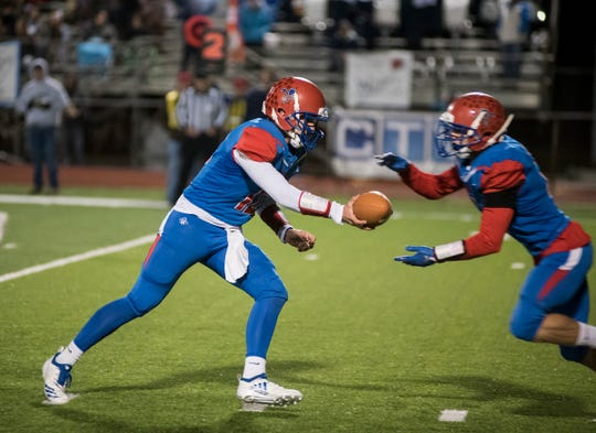 St. Clair High School quarterback Brady Gleason (left) hands off the ball during their division 4 district finals game against North Branch Saturday, Nov. 3, 2018 at East China Stadium.