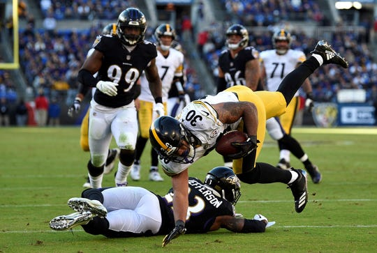 Pittsburgh Steelers running back James Conner (30) tries to stay on his feet as he rushes against Baltimore Ravens strong safety Tony Jefferson in the second half of an NFL football game, Sunday, Nov. 4, 2018, in Baltimore. (AP Photo/Nick Wass)