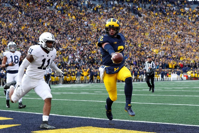Michigan quarterback Shea Patterson (2) scores on a one-yard touchdown run as Penn State linebacker Micah Parsons (11) defends in the first half of an NCAA college football game in Ann Arbor, Mich., Saturday, Nov. 3, 2018. (AP Photo/Paul Sancya)