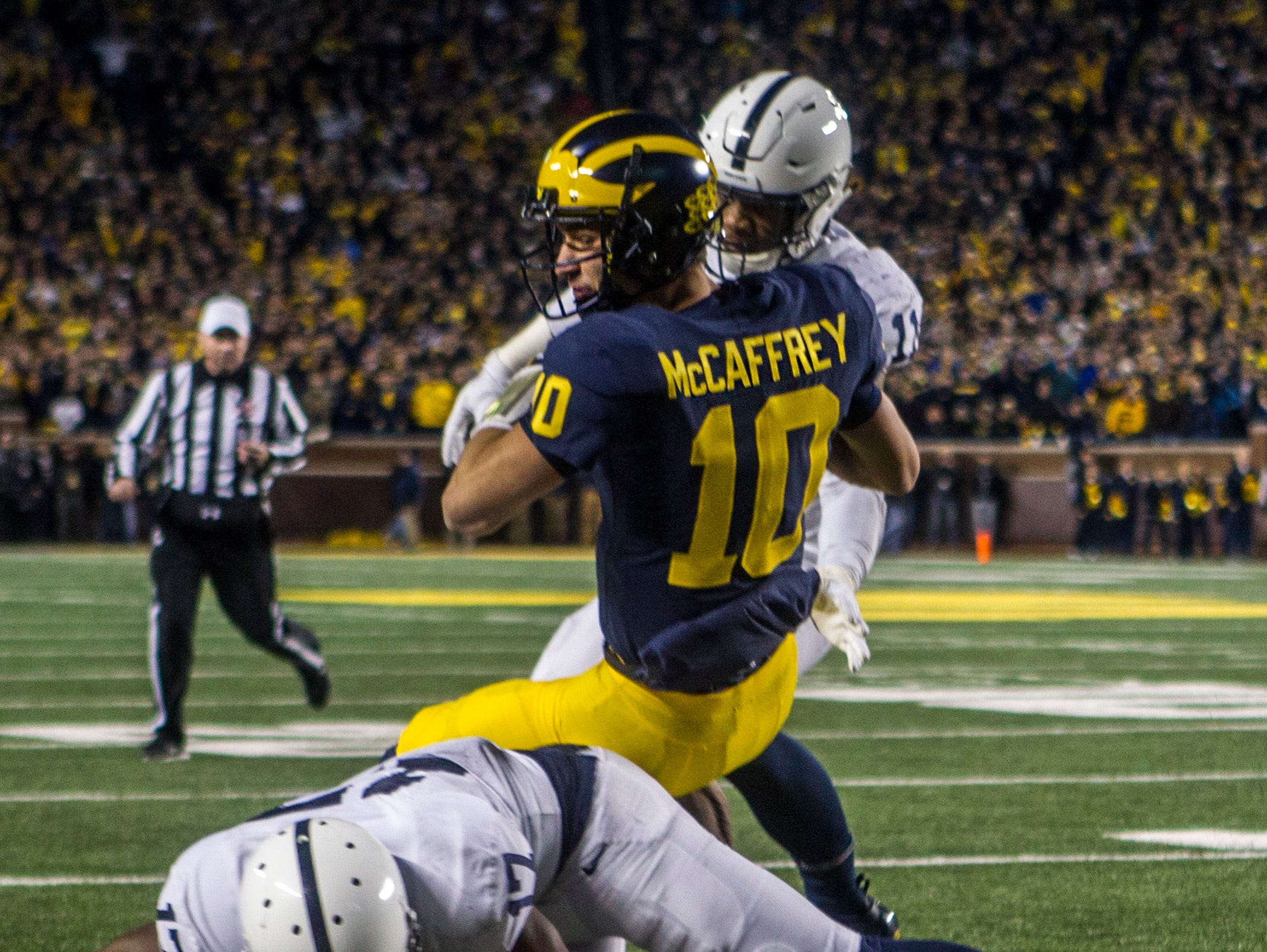 Michigan quarterback Dylan McCaffrey (10) is forced out of bounds short of the goal line by Penn State safety Garrett Taylor (17) and linebacker Micah Parsons (11), in the fourth quarter of an NCAA college football game in Ann Arbor, Mich., Saturday, Nov. 3, 2018. (AP Photo/Tony Ding)