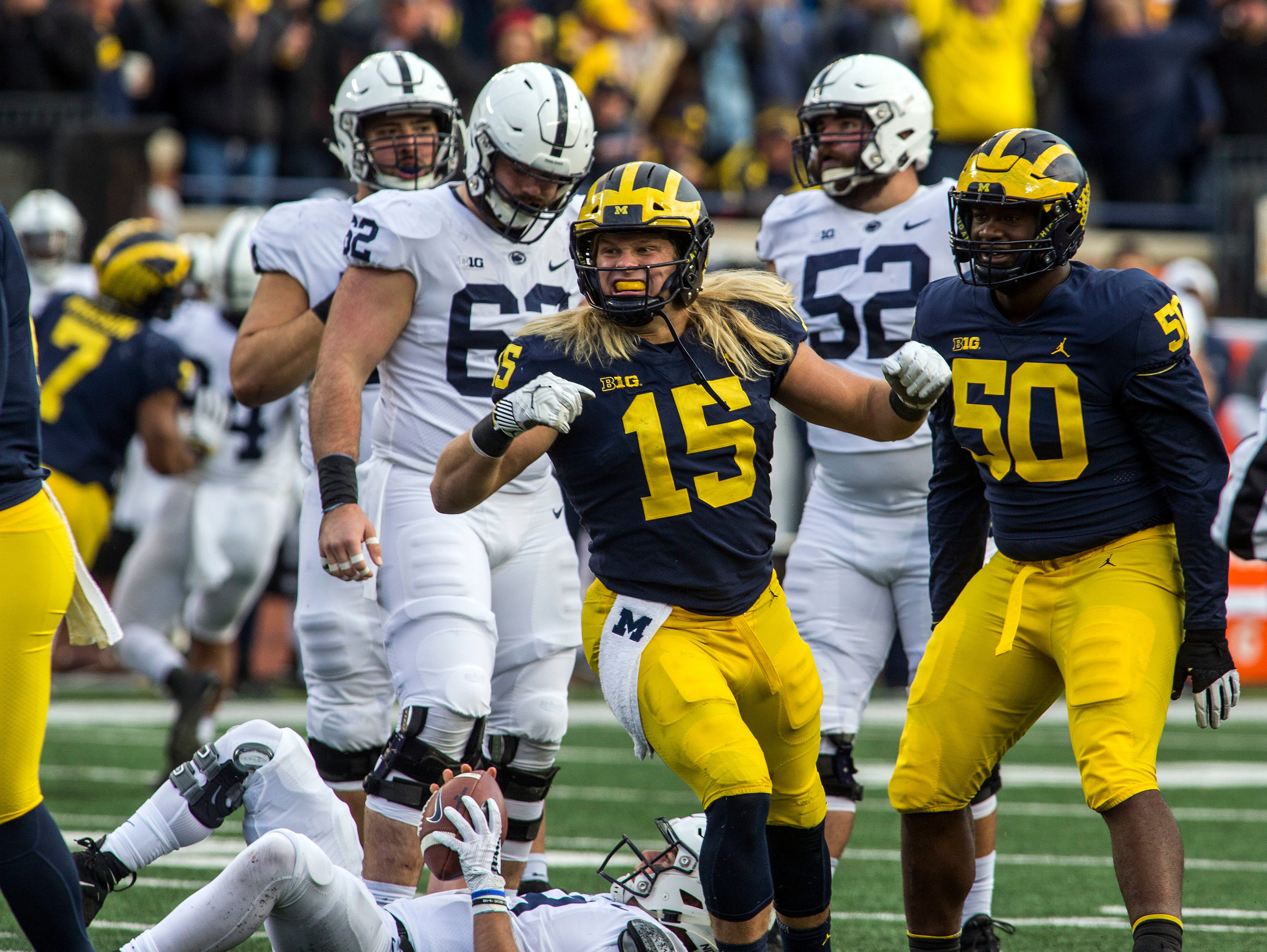 Michigan defensive lineman Chase Winovich (15) celebrates with defensive lineman Michael Dwumfour (50) a sack of Penn State quarterback Trace McSorley, bottom, in the third quarter of an NCAA college football game in Ann Arbor, Mich., Saturday, Nov. 3, 2018. Michigan won 42-7. (AP Photo/Tony Ding)