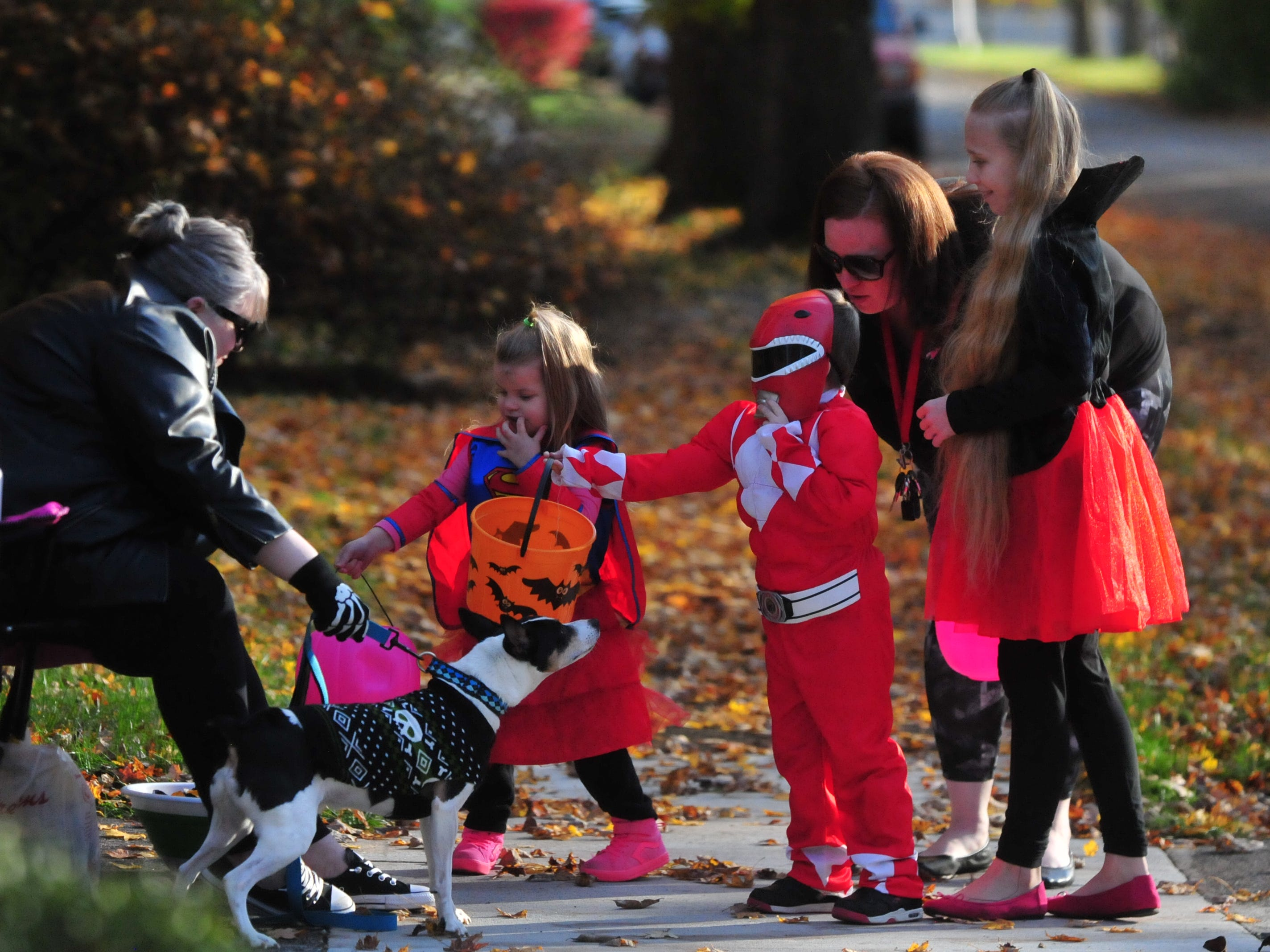 Julie Alexander and Cody pass out candy to trick-or-treaters Alayna McDaniel, 3; Talyn McDaniel, 4; and Taryn McDaniel, 10, who went trick-or-treating Saturday with Ashley McDaniel.