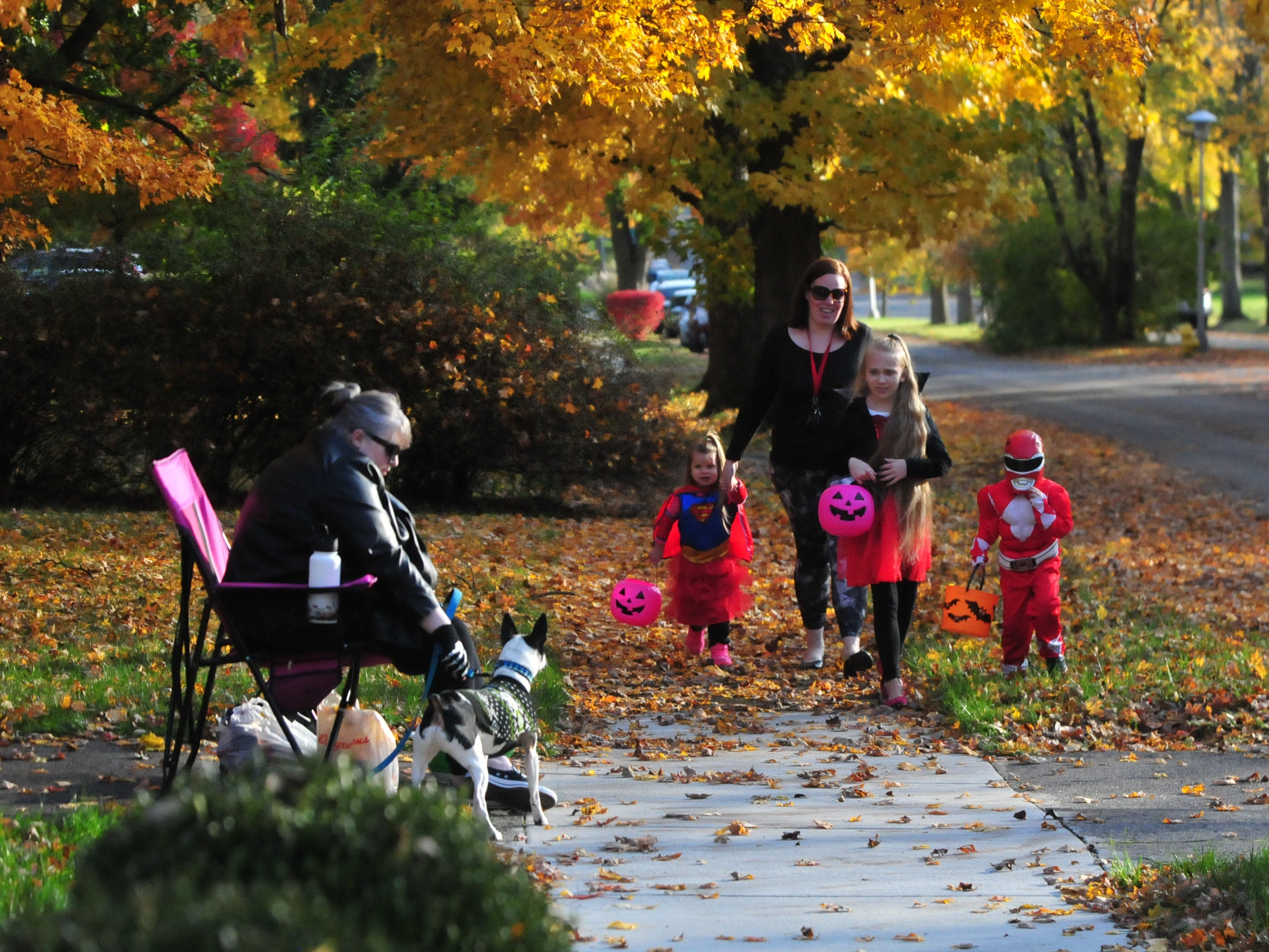 Julie Alexander and Cody wait for Ashley McDaniel and her trick-or-treaters Alayna, 3; Taryn, 10; and Talyn, 4, during Saturday's Richmond trick-or-treat time.