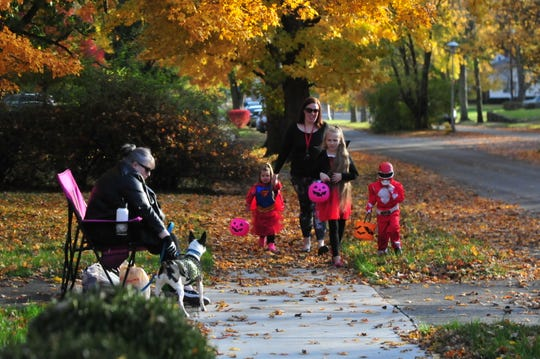 Julie Alexander and Cody wait for Ashley McDaniel and her trick-or-treaters Alayna, 3; Taryn, 10; and Talyn, 4, during trick-or-treating in Richmond in 2018.