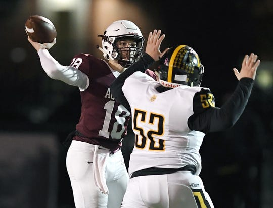 Aquinas' Tyler Szalkowski, left, throws a pass while pressured by McQuaid's Tim Fournier during the Section V Class AA championship game at SUNY Brockport, Saturday, Nov. 3, 2018. Aquinas won the Class AA title with a 49-18 win over McQuaid.