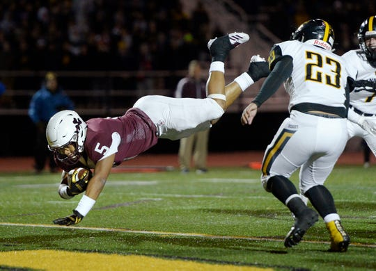 Aquinas' Ruben Torres dives across the goal line for Aquinas' second touchdown during the Section V Class AA championship game at SUNY Brockport, Saturday, Nov. 3, 2018.