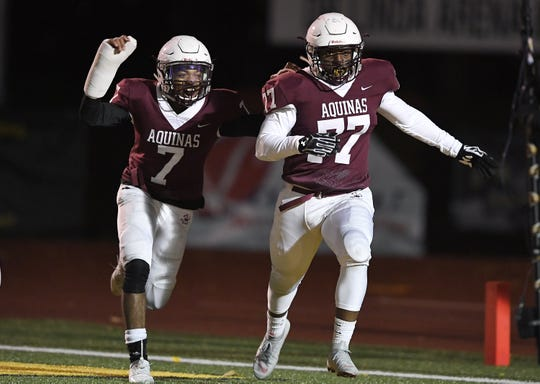 Aquinas' James Waters, right, celebrates his fumble recovery touchdown with Caron Robinson during the Section V Class AA championship game at SUNY Brockport, Saturday, Nov. 3, 2018. Aquinas won the Class AA title with a 49-18 win over McQuaid.