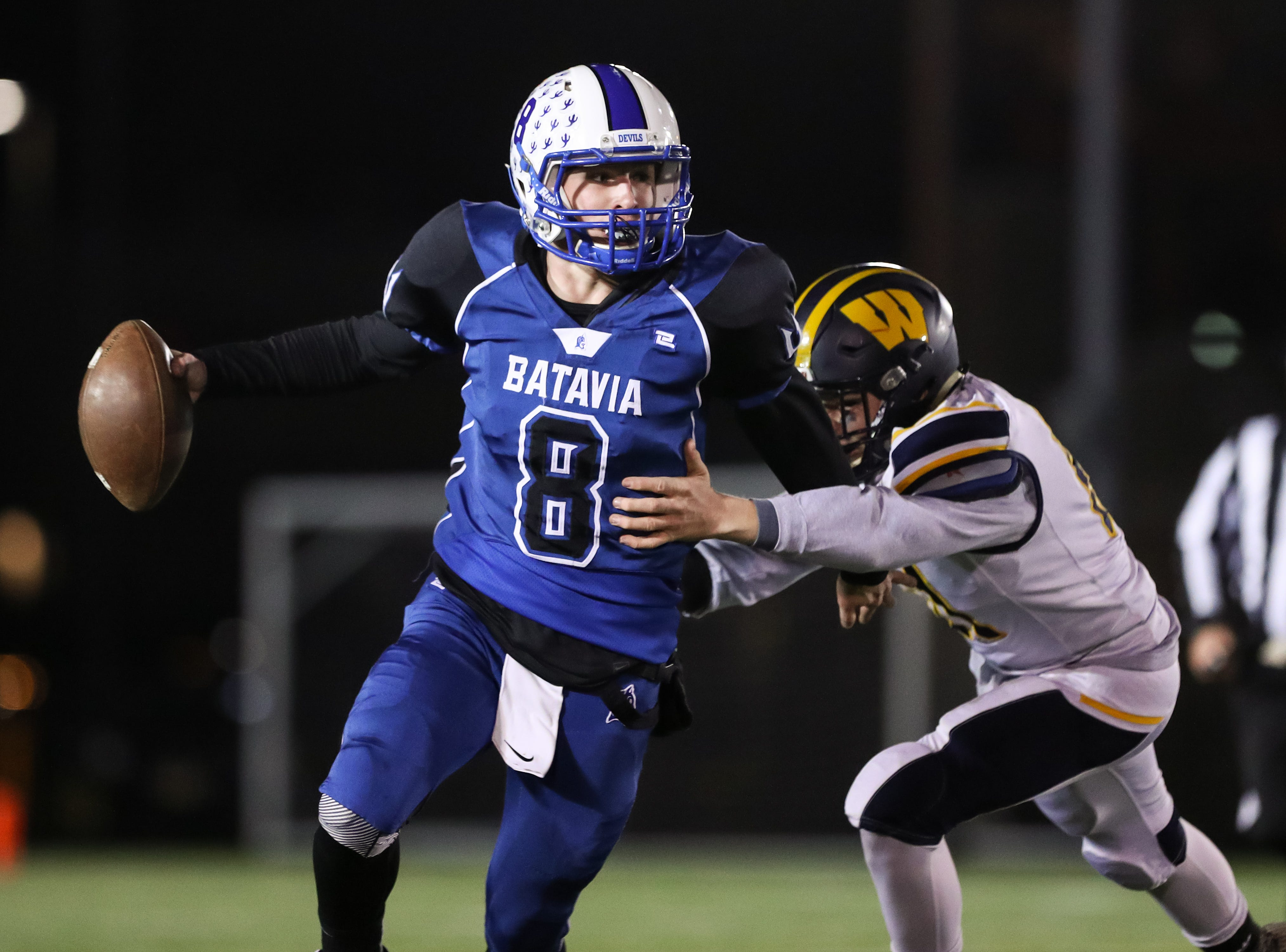 Batavia Blue Devils quarterback Ethan Biscaro avoids a pass rusher.