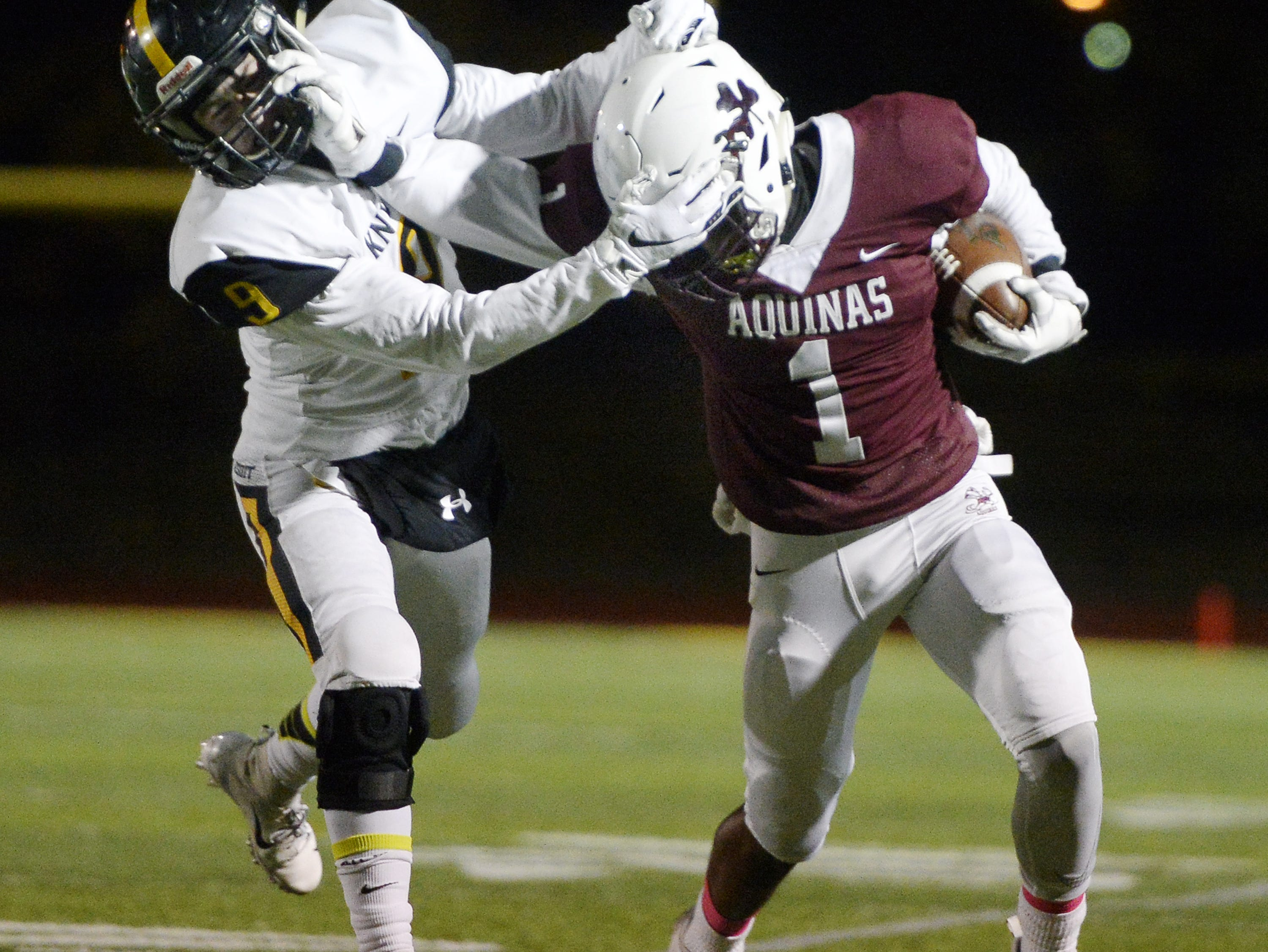 Aquinas' Ulysees Russell, right, tries to break free of McQuaid's Ben Beauchamp during the Section V Class AA championship game at SUNY Brockport, Saturday, Nov. 3, 2018. Aquinas won the Class AA title with a 49-18 win over McQuaid.