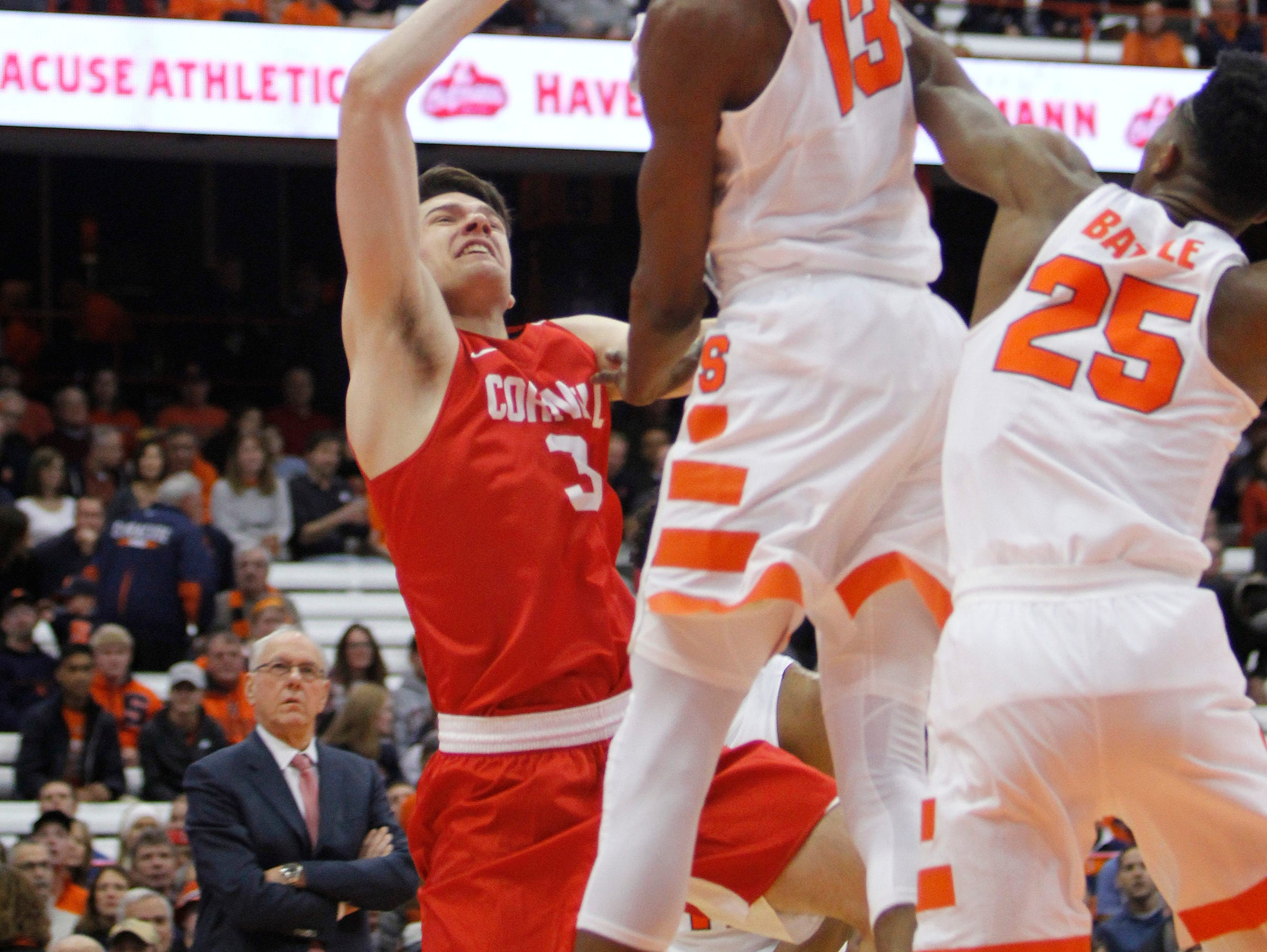Syracuse head coach Jim Boeheim (3) watches his son, Cornell's Jimmy Boeheim, right, battle for a rebound against Syracuse's Paschal Chukwu and Tyus Battle in the first half of an NCAA college basketball game in Syracuse, N.Y., Friday, Nov. 10, 2017. (AP Photo/Nick Lisi)
