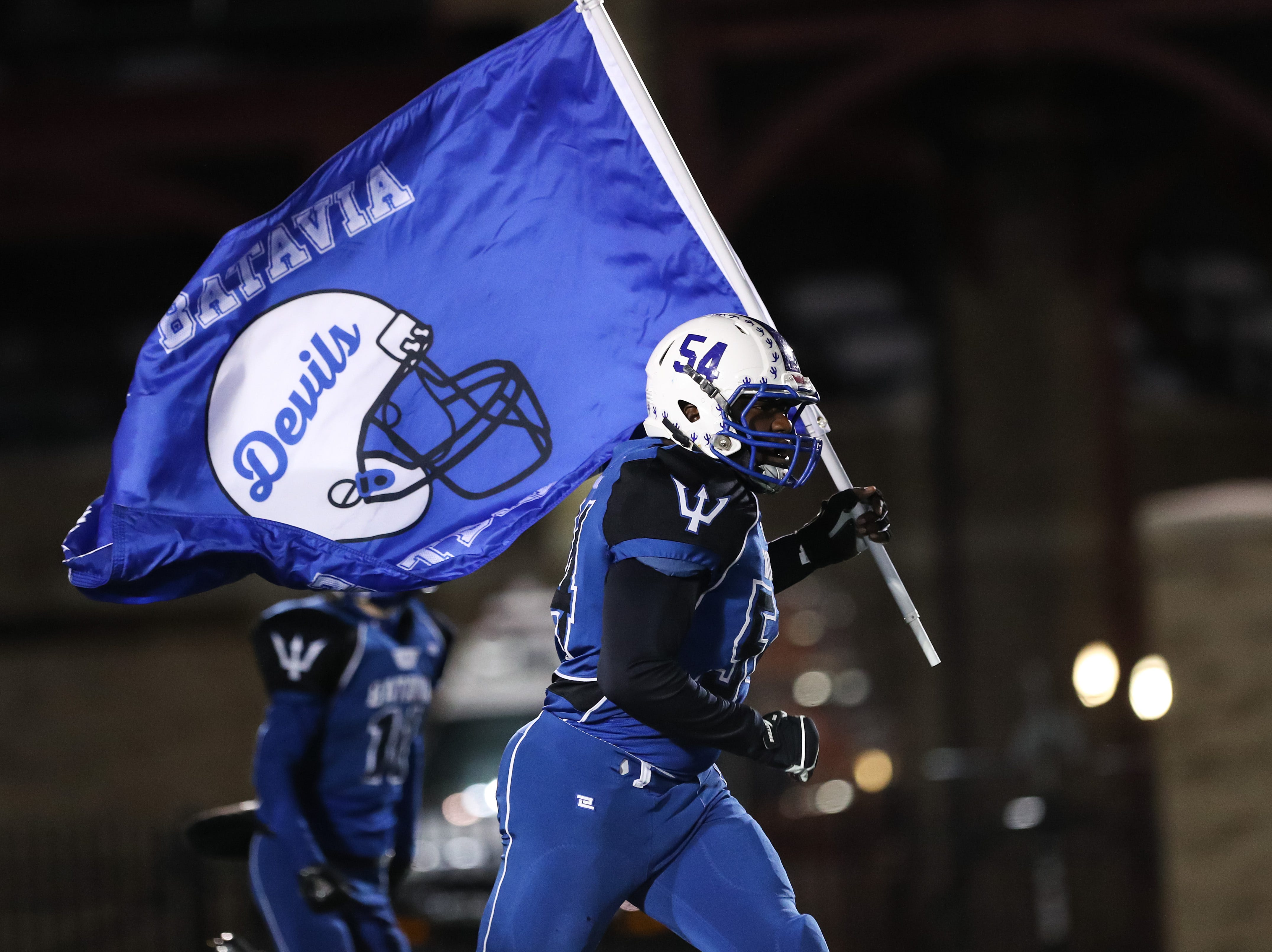 Batavia Blue Devils Josh Barber runs onto the field with the flag before the  Section V Class B championship high school football game against the Wayne Eagles.