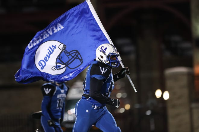 Batavia's Josh Barber runs onto the field with the flag before the  Section V Class B championship high school football game against the Wayne Eagles.