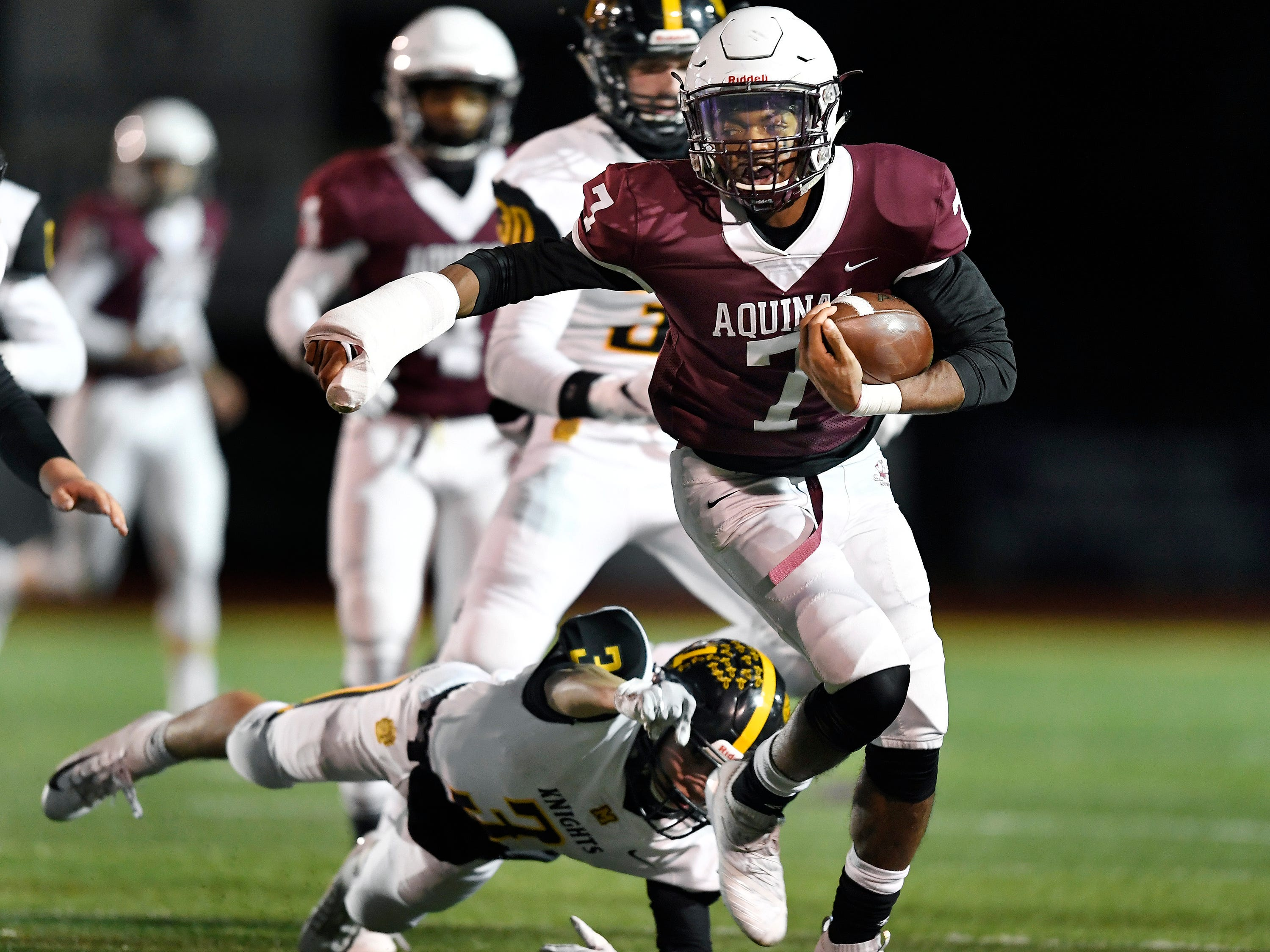 Aquinas' Caron Robinson, right, breaks a tackle by McQuaid's Andrew Passero on his way to a 56-yard touchdown during the Section V Class AA championship game at SUNY Brockport, Saturday, Nov. 3, 2018.