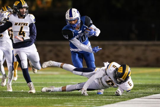 Batavia Blue Devils wide receiver Taiyo Iburi-Bethel tries to avoid Wayne Eagles linebacker John Reagan.