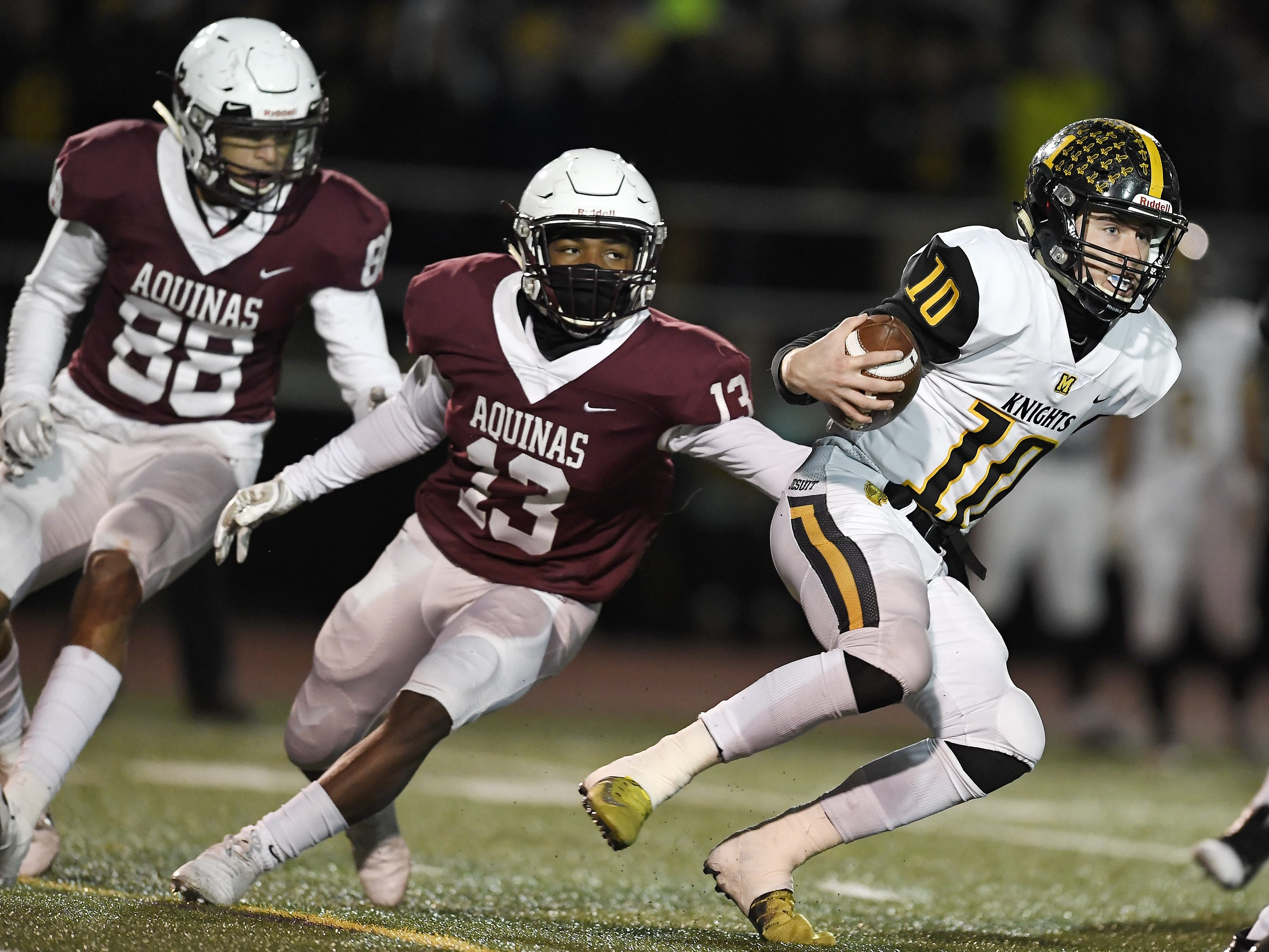 McQuaid's Hunter Walsh, right, tries to elude the pressure by Aquinas' Will Benjamin (13) and Steve Mahar (88) during the Section V Class AA championship game at SUNY Brockport, Saturday, Nov. 3, 2018. Aquinas won the Class AA title with a 49-18 win over McQuaid.