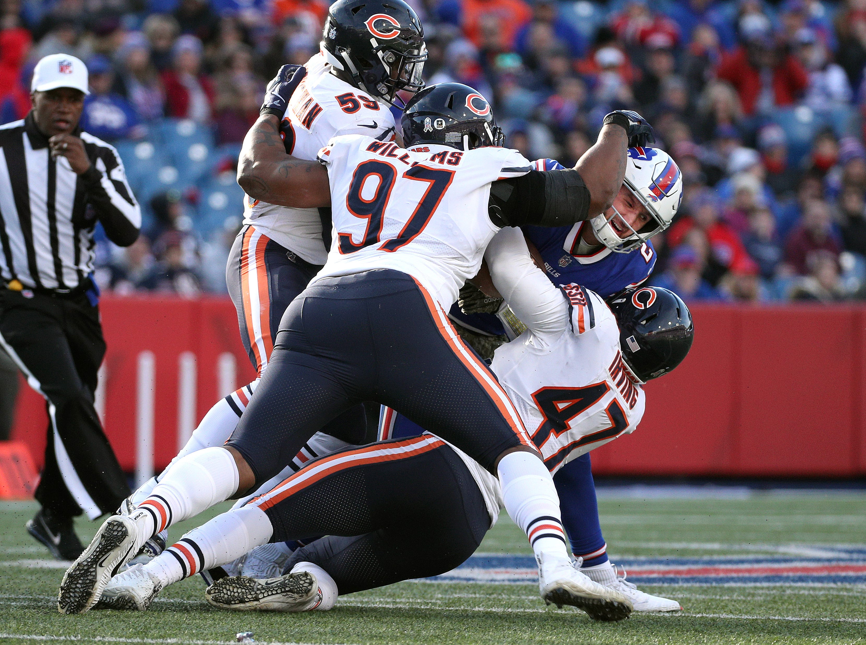 Nathan Peterman is smothered by Bears defenders Nick Williams (97), Isaiah Irving (47) and Danny Trevathan.