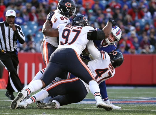 Bills QB Nathan Peterman is smothered by Bears defenders Nick Williams (97), Isaiah Irving (47) and Danny Trevathan.