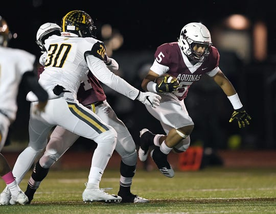 Aquinas' Ruben Torres breaks through a hole in the line of scrimmage during the Section V Class AA championship game at SUNY Brockport, Saturday, Nov. 3, 2018. Aquinas won the Class AA title with a 49-18 win over McQuaid.
